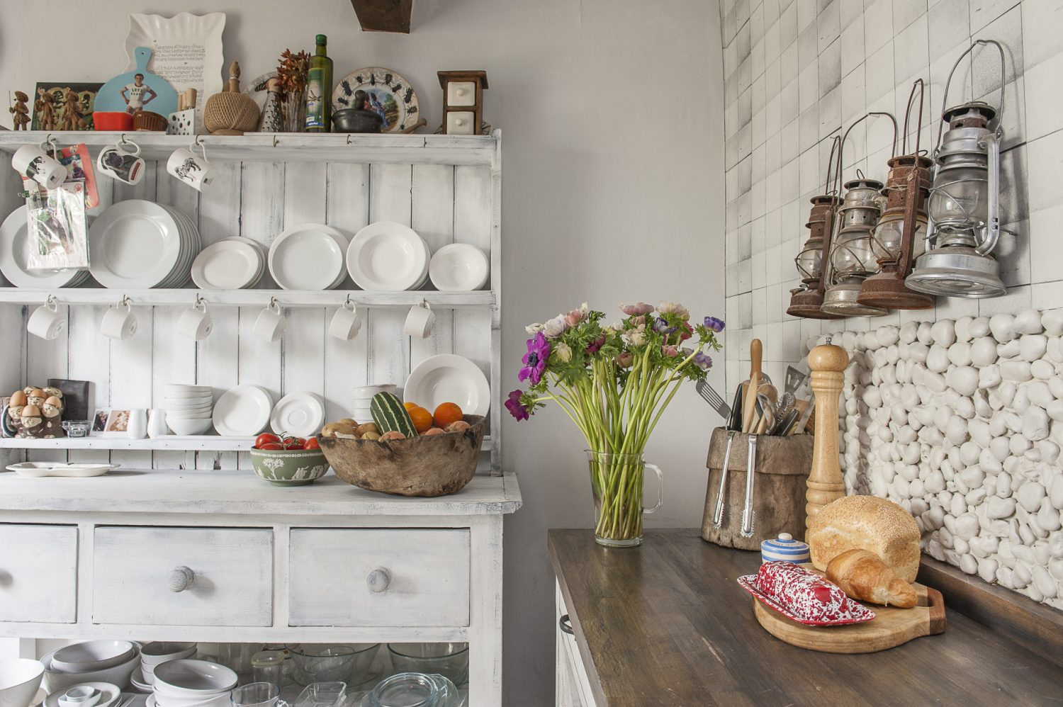 Painted pebbles make a textural splashback above the wooden worktop