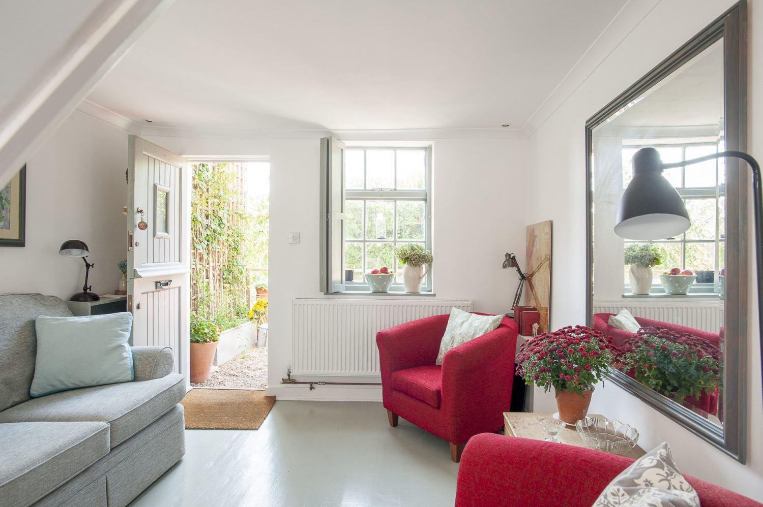 The living room is clean, crisp, comfortable and welcoming, the white walls set off with a grey sofa and red armchairs. There is no fireplace and so Linda has given the room a focal point with a large and elegant mirror