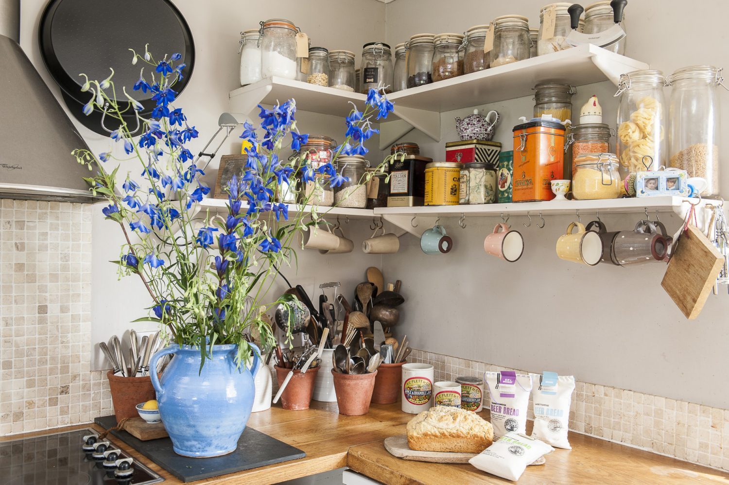 Rather than tucking them away in a cupboard, Tina's neatly labelled Kilner jars – lined up on shelves above the worksurface – ensure that dry ingredients are always to hand