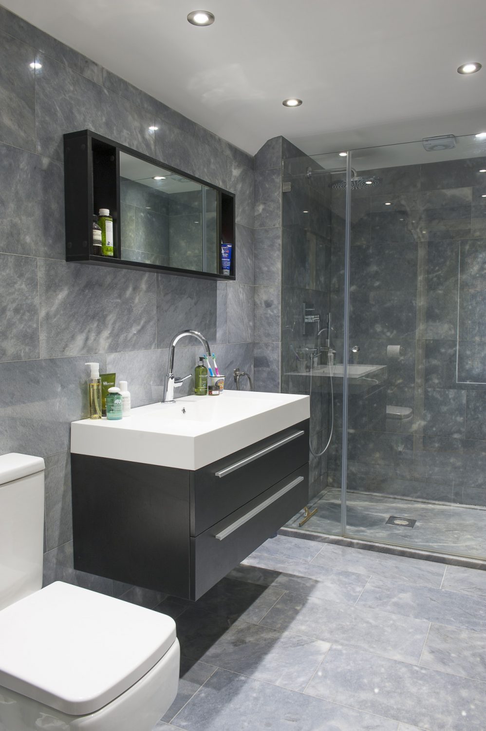 Sally has broken with the traditional style of the rest of the house by installing a contemporary en suite shower room with floor to ceiling grey marble and lacquered black units.