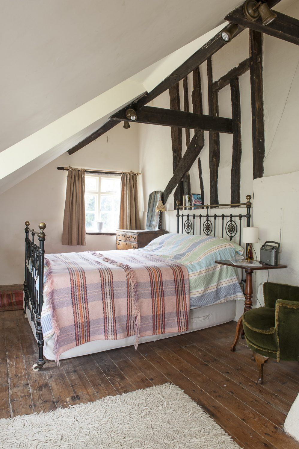 A cosy guest bedroom enjoys privacy up on the top floor of the house