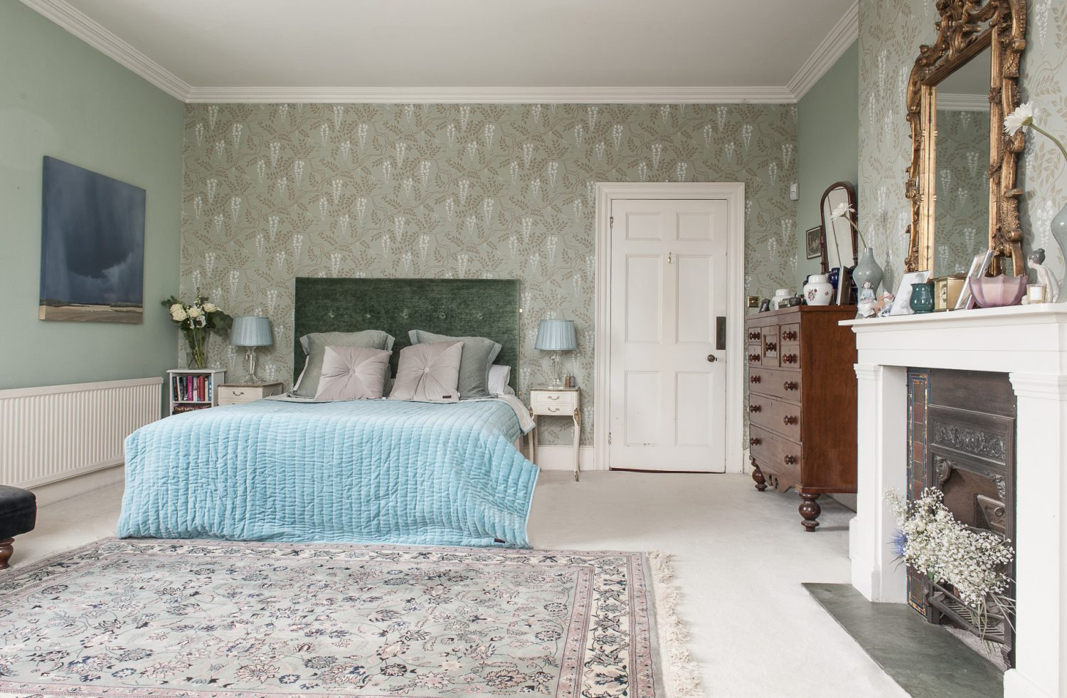 The double-aspect master bedroom is Dawn's favourite room. The green marble hearth of the Edwardian fireplace dictated the overall colour scheme, with Dawn opting for a Cole & Son wallpaper printed with Wisteria
