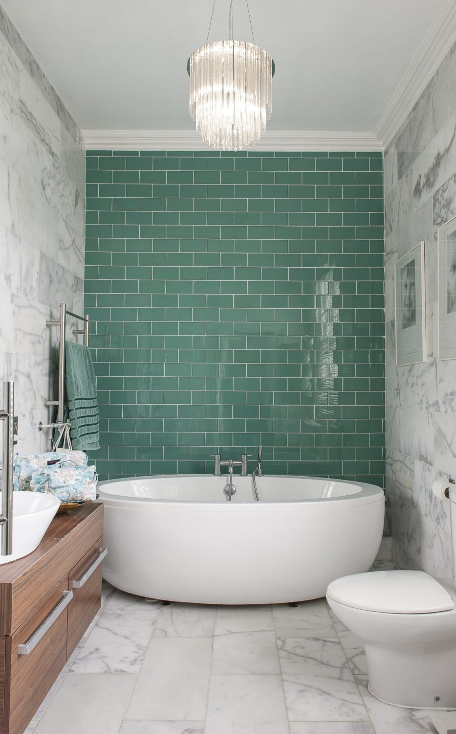 The turquoise-tiled rear wall of Dawn's en suite bathroom is flanked by floor-to-ceiling white marble