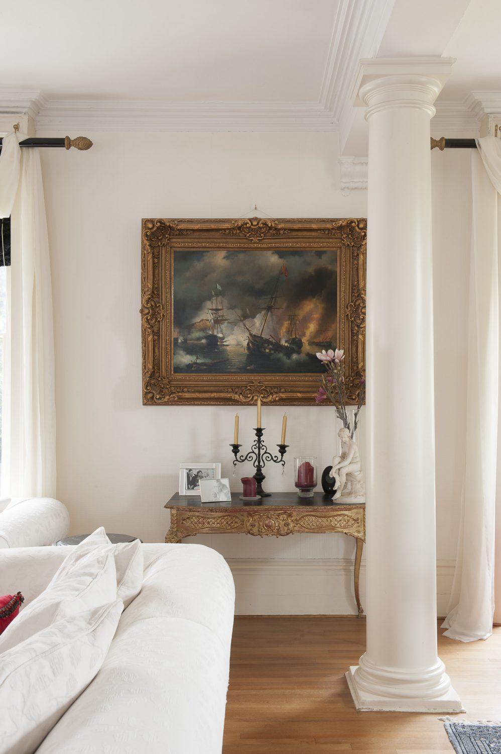 A sizable oil painting of a naval battle hangs above a gilded table