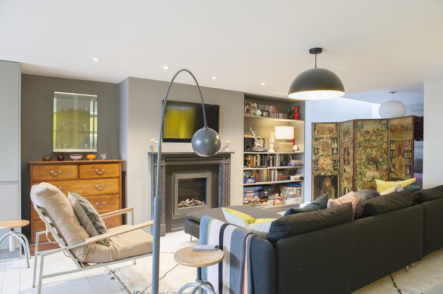 The basement apartment offers an independent space for guests, with the bed concealed behind a vintage decoupaged screen from AG Hendy & Co in Hastings Old Town. There is a recessed television over the vintage slate fireplace. The grey metal standard lamp is from Heals and the ceiling fitting is one of a pair by Habitat, black with a bright yellow interior the same as the feature wall