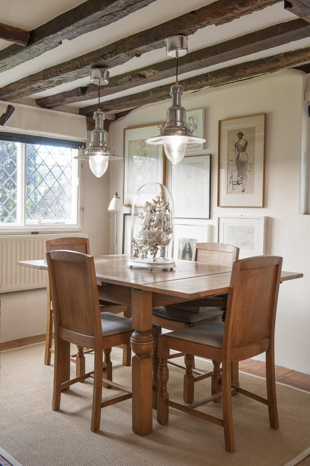 Hanging above the dining table and chairs, sourced from SV Antiques, is a pair of old stainless steel industrial lights. A few of Roni's sketches are mounted in frames on the wall between life drawings and charcoal studies