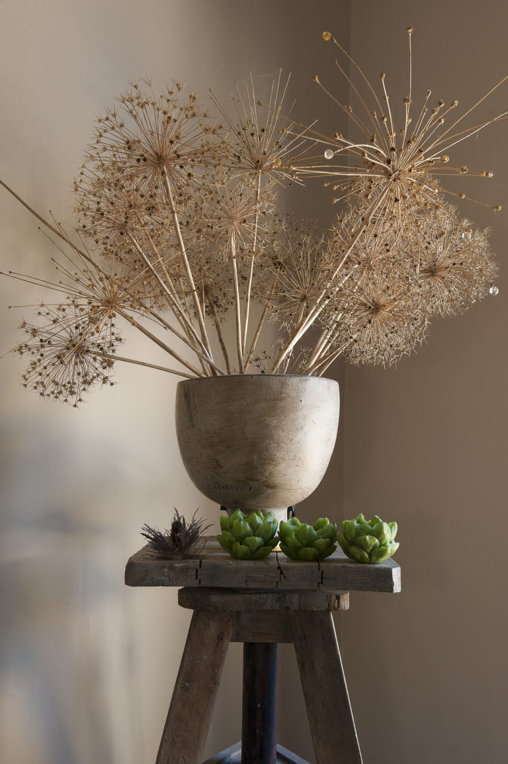 A sculptor's revolving plinth holds an arrangement of dried allium heads and artichoke-style candles