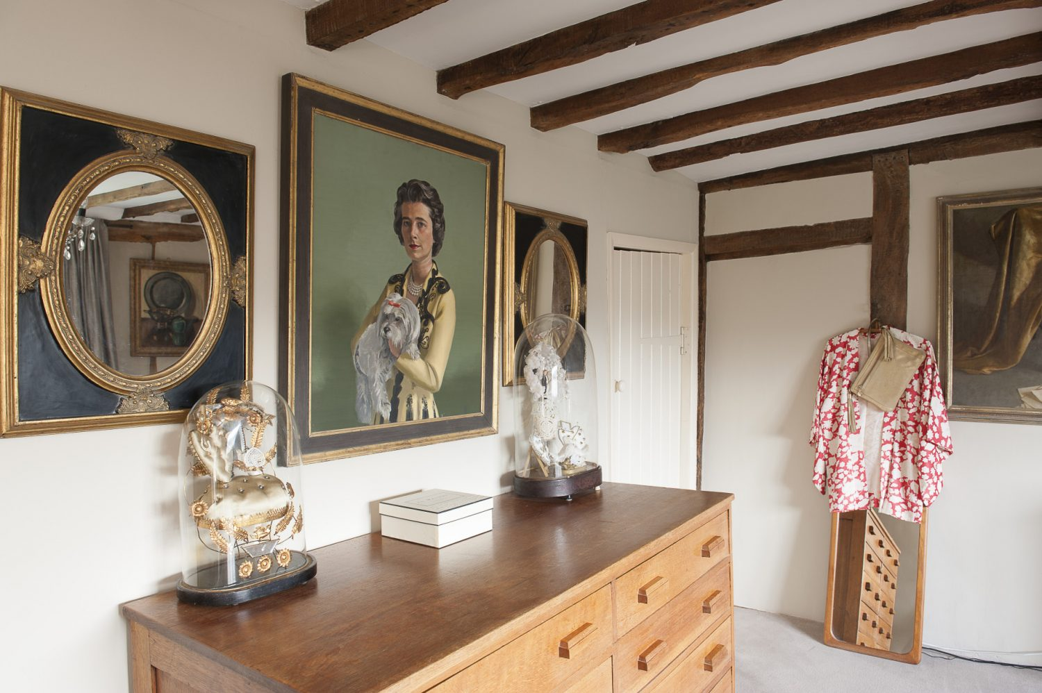 Opposite the master bedroom window is another 1950s portrait from a Westerham antiques shop, flanked by two oval gilt and black mirrors; beneath, atop a 1930s oak chest of drawers, are two more favourite domes