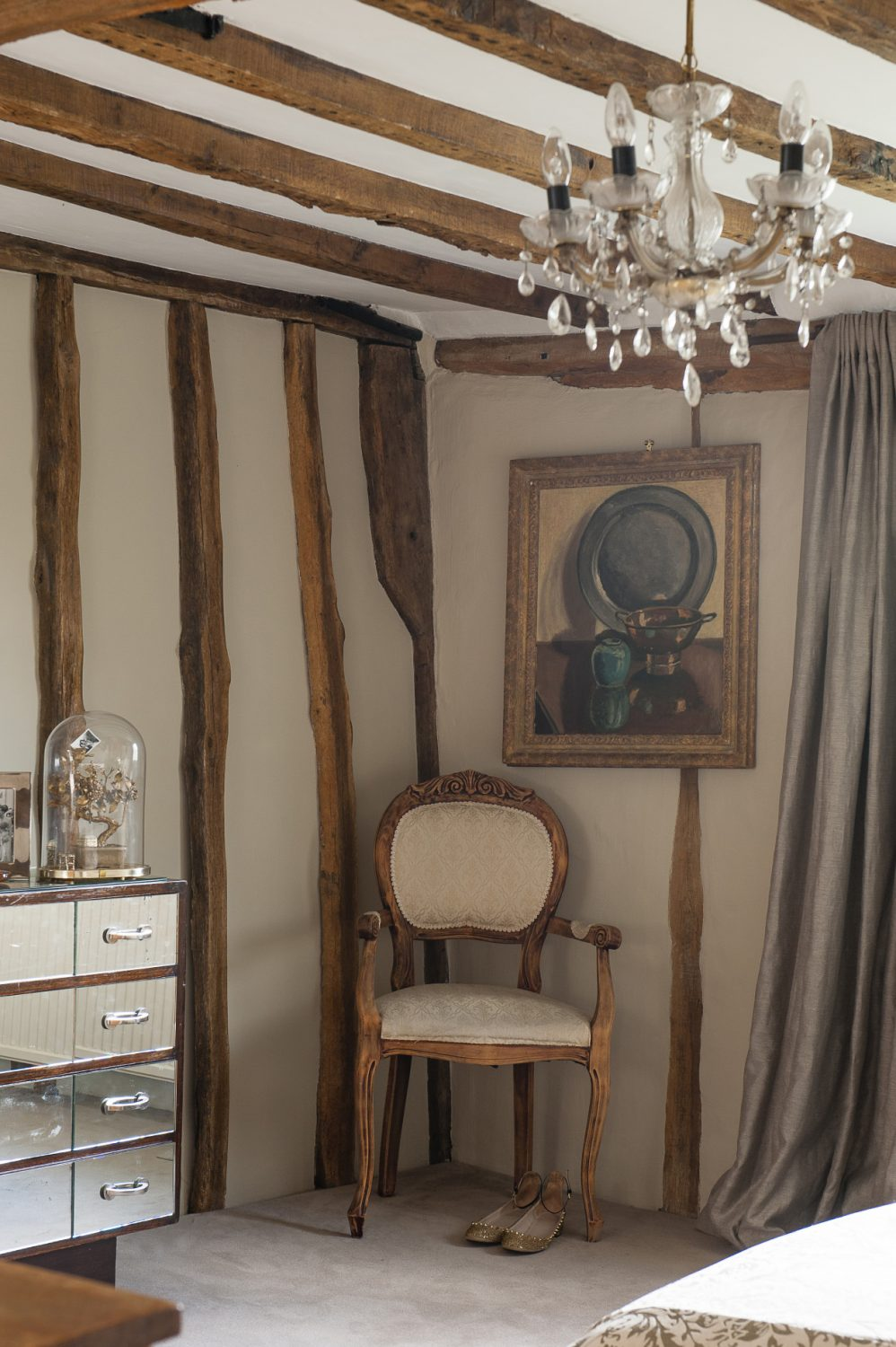 Adjacent to a stunning 1920s mirrored chest of drawers, a still life hangs above a gilded chair in one co
