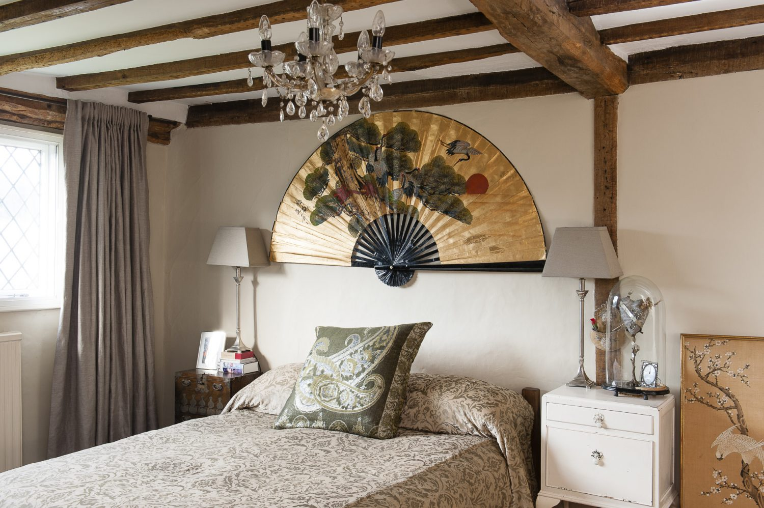 A glowing gold oriental fan takes centrestage in the master bedroom. Beside the bed is Roni and John's own wedding dome.
