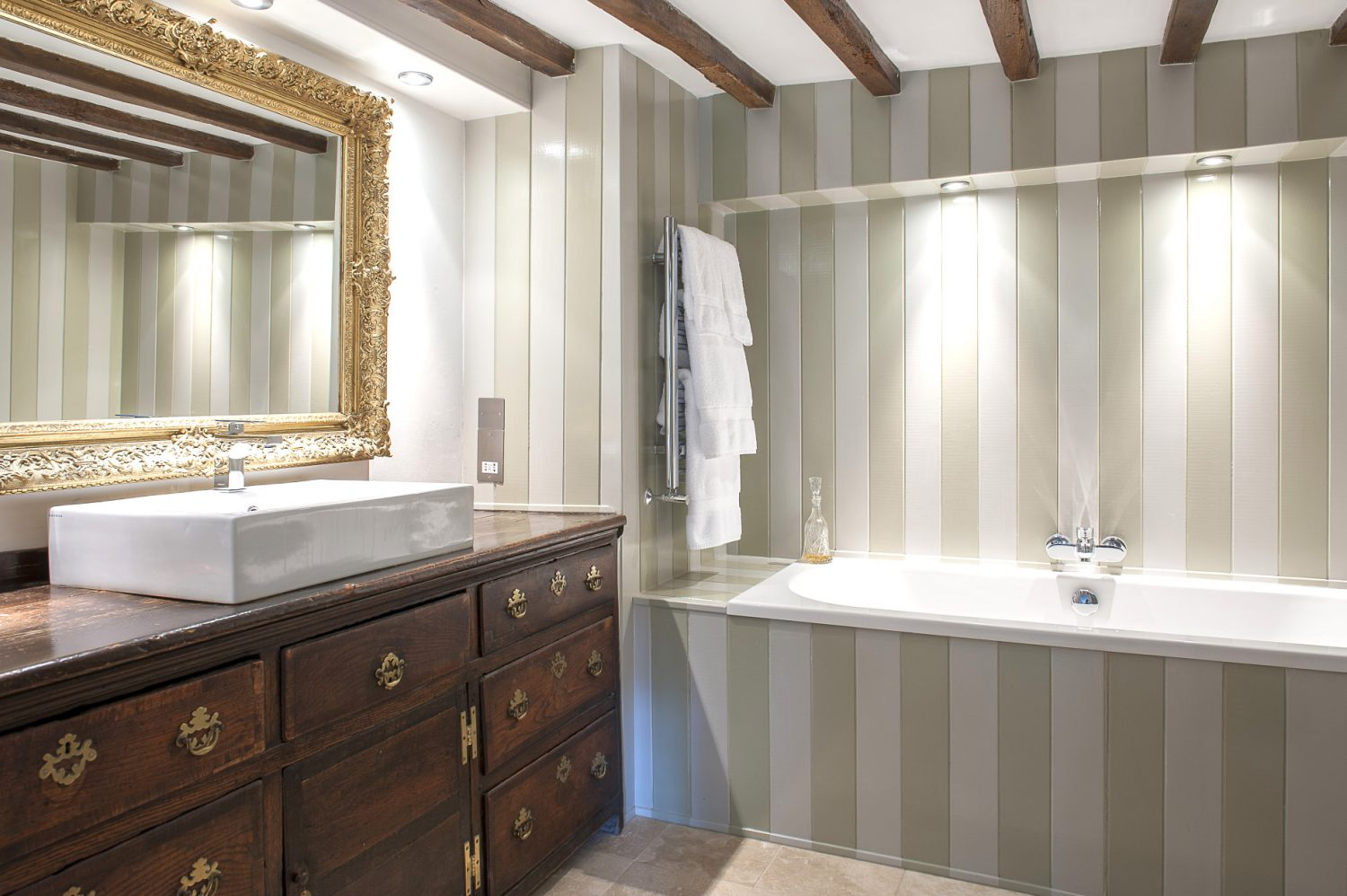 The wood panelled en suite features a Georgian dresser which exactly fitted the space that Matthew had earmarked for a contemporary basin