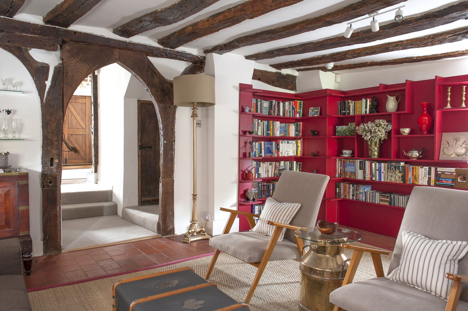 On the ground floor, a timbered Gothic arch leads through to the sitting room, fitted with a contemporary shelving unit painted a vibrant Farrow & Ball Rectory Red. Between two Scandinavian armchairs is a highly polished milk churn on top of which has been placed a piece of circular glass to make an unusual and attractive side table