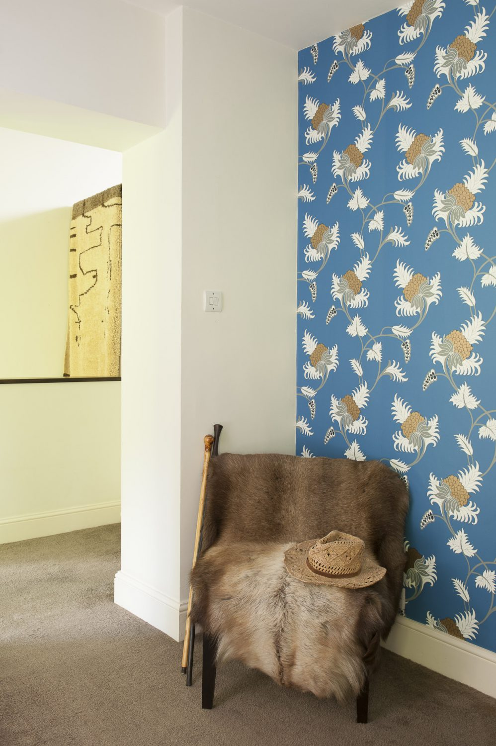 A reindeer hide thrown over a chair creates a dramatic corner on the upstairs landing. The bold pineapple print wallpaper is Neisha Crosland