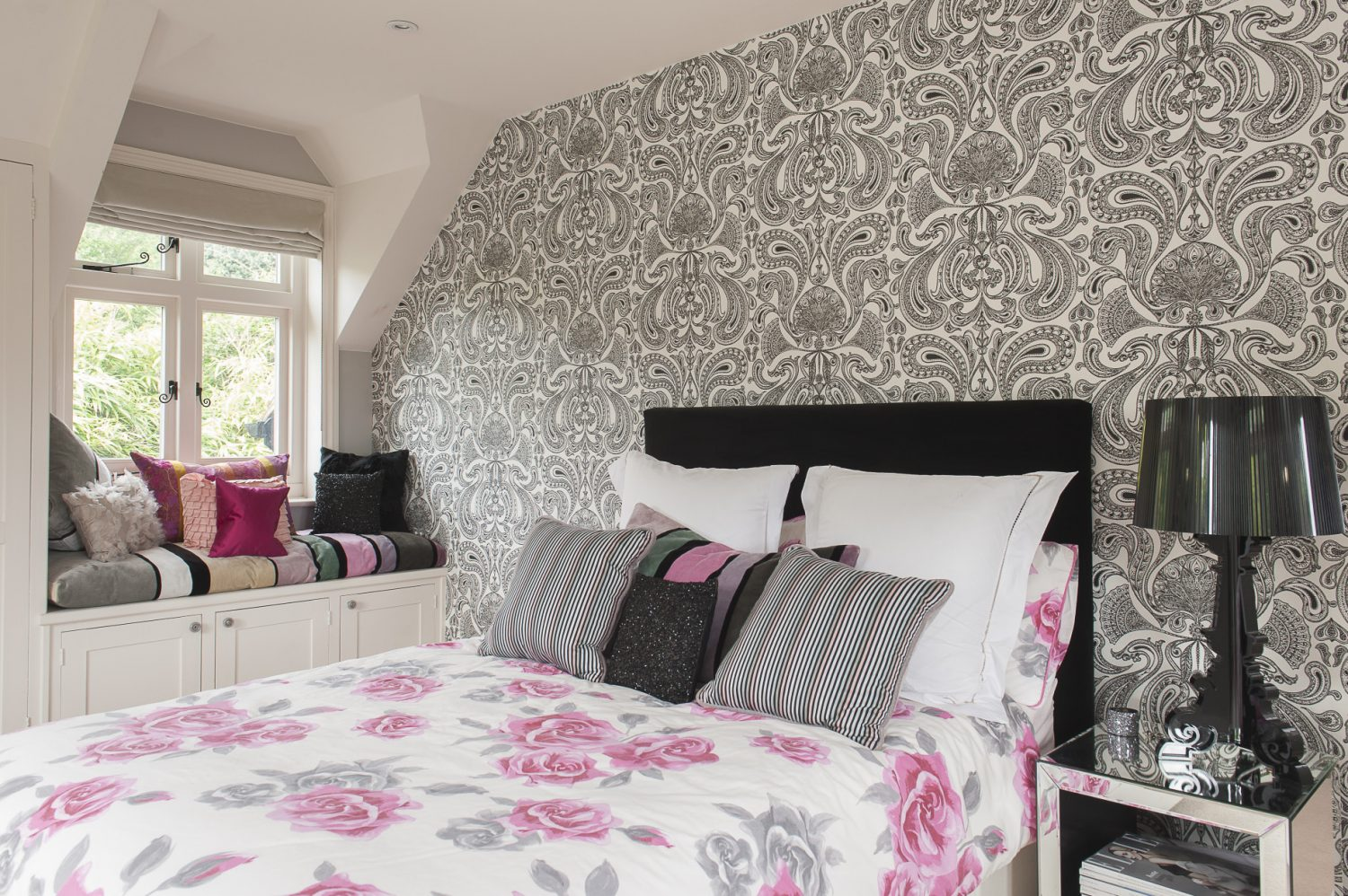 Daughter Georgia has gone for a cross between monochrome and Miami for her bedroom with hot pink accents mixed in with the striking black and white paisley wallpaper by Cole & Son. The bedside lamp is by Kartell