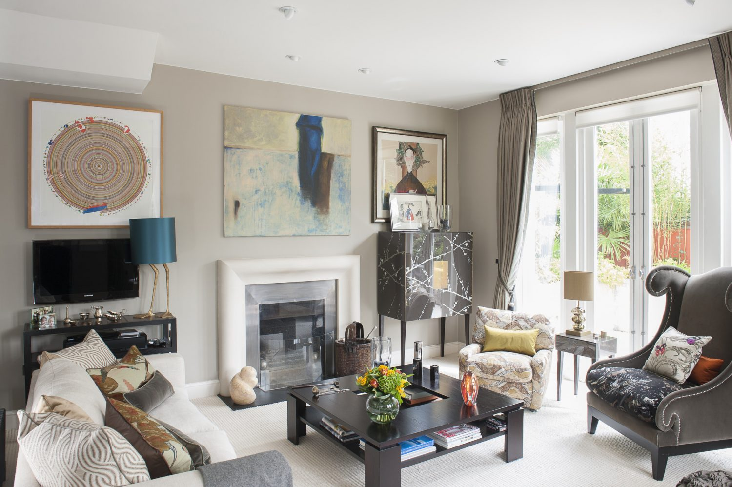 The drawing room has glass doors opening on to a courtyard. The fireplace is finished with a Chesney's limestone surround and stainless steel insert. Jane and Chris are keen art collectors. They bought the abstract painting above the fire during a holiday in Sri Lanka. The Modigliani-style portrait is by a Vietnamese artist, found at an Affordable Art Fair. The duck feet lamp is by Porto Romana