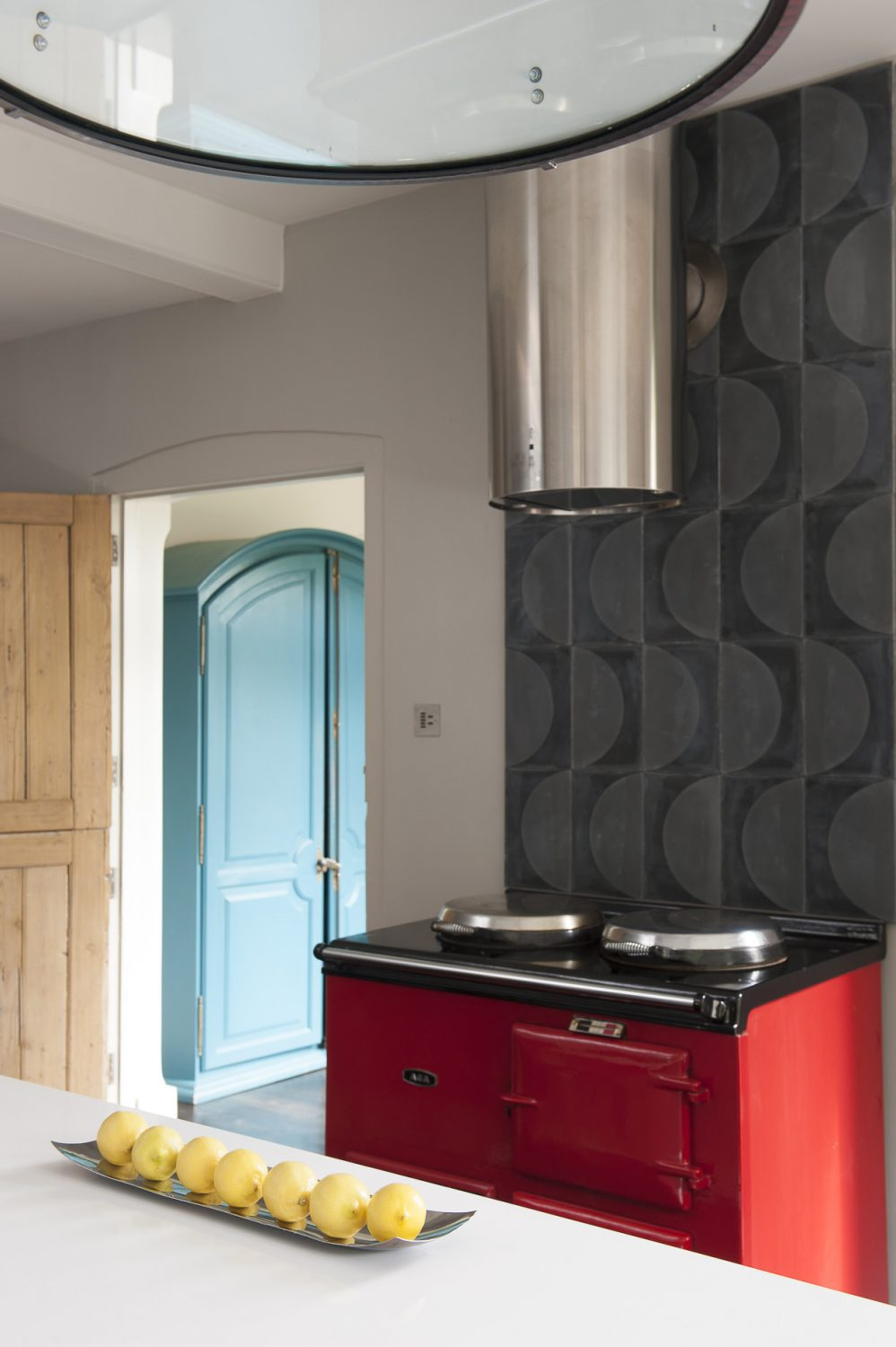 Although Jane's scheme was designed around a cool white central island with a gas hob, she didn't want to lose the familiar warmth of the 1970s family Aga, which now adds a bold red accent to the ultra contemporary industrial mood of the kitchen