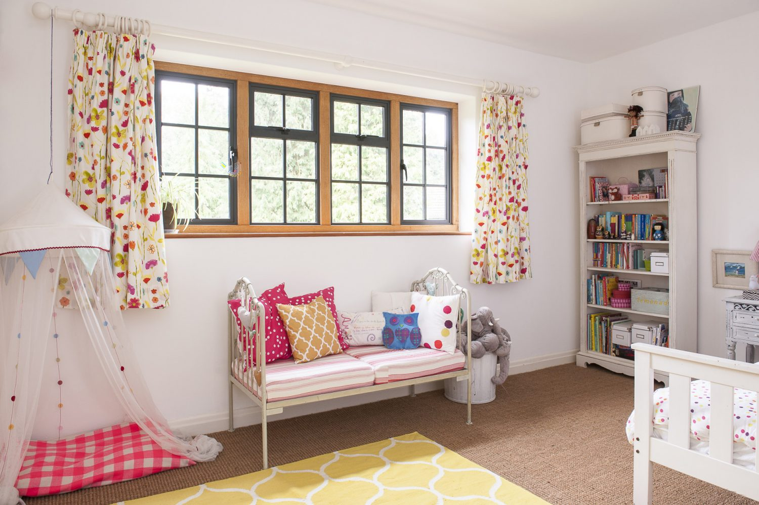 Amber's room is painted in a 'simple white' but livened up with bright and cheerful fabrics. Kate, rescued the miniature wrought iron day bed from a florist's shop, where it was being used for display. Original oak mullion windows throughout the house are a reminder of its 1920s origin