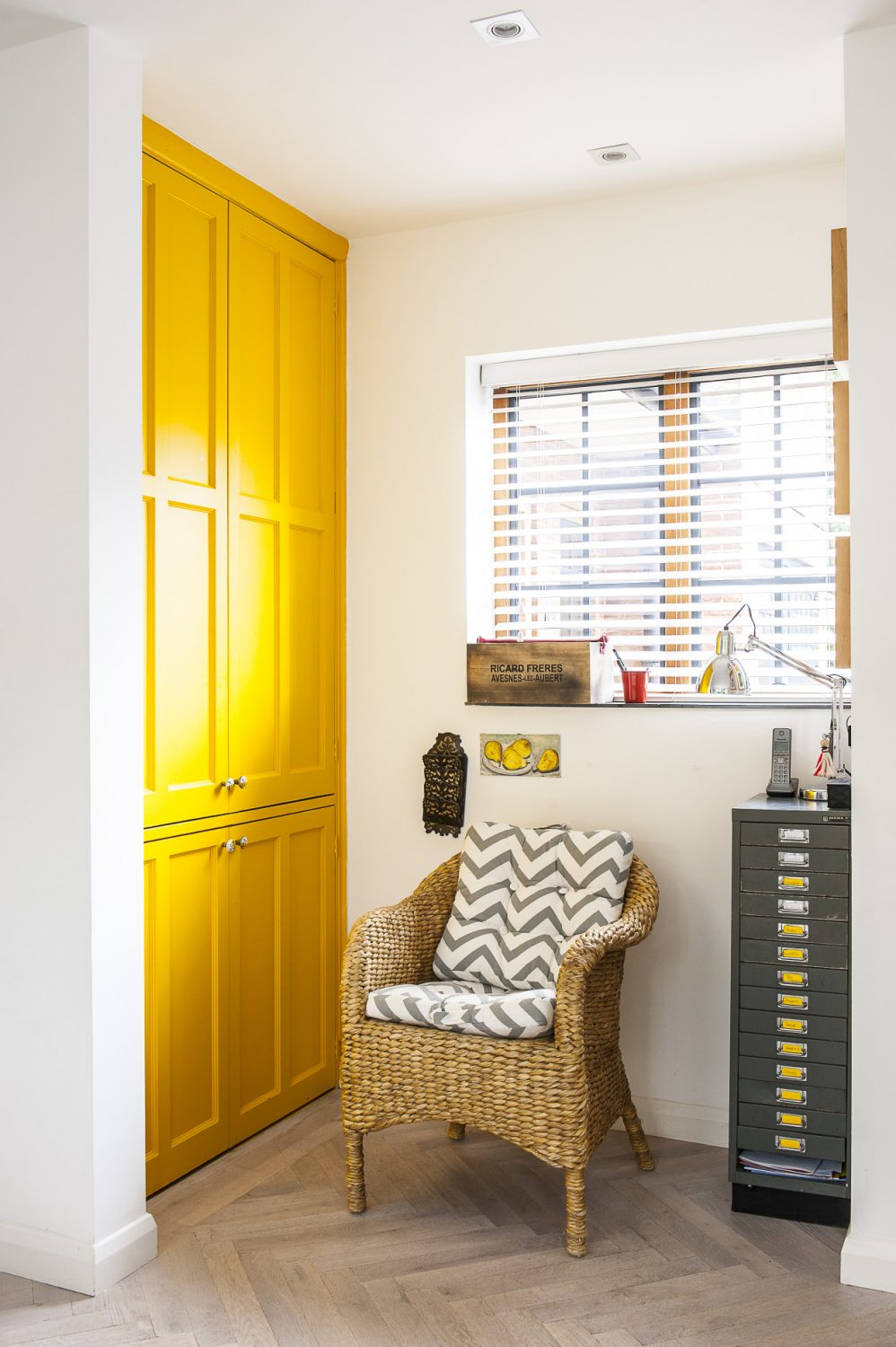 The 'simple yellow' of the Tesco bar stools in the kitchen is echoed by lamps in the living room and the painted doors of a downstairs storage cupboard.