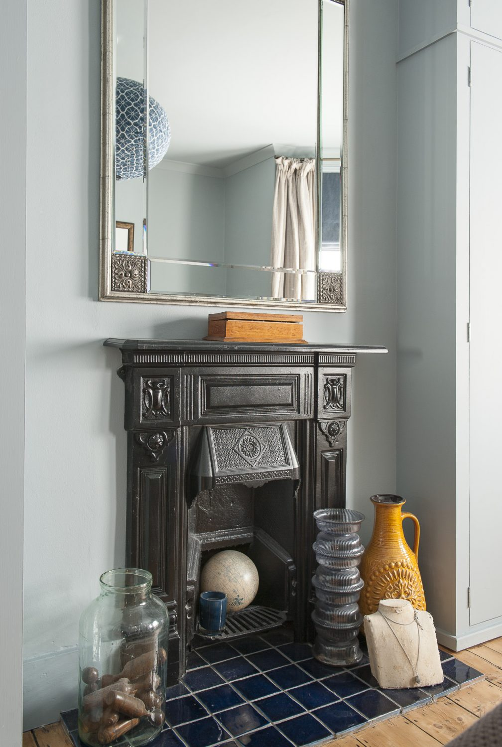 An original fireplace makes the perfect focal point for the room and a collection of 'objets trouvés'