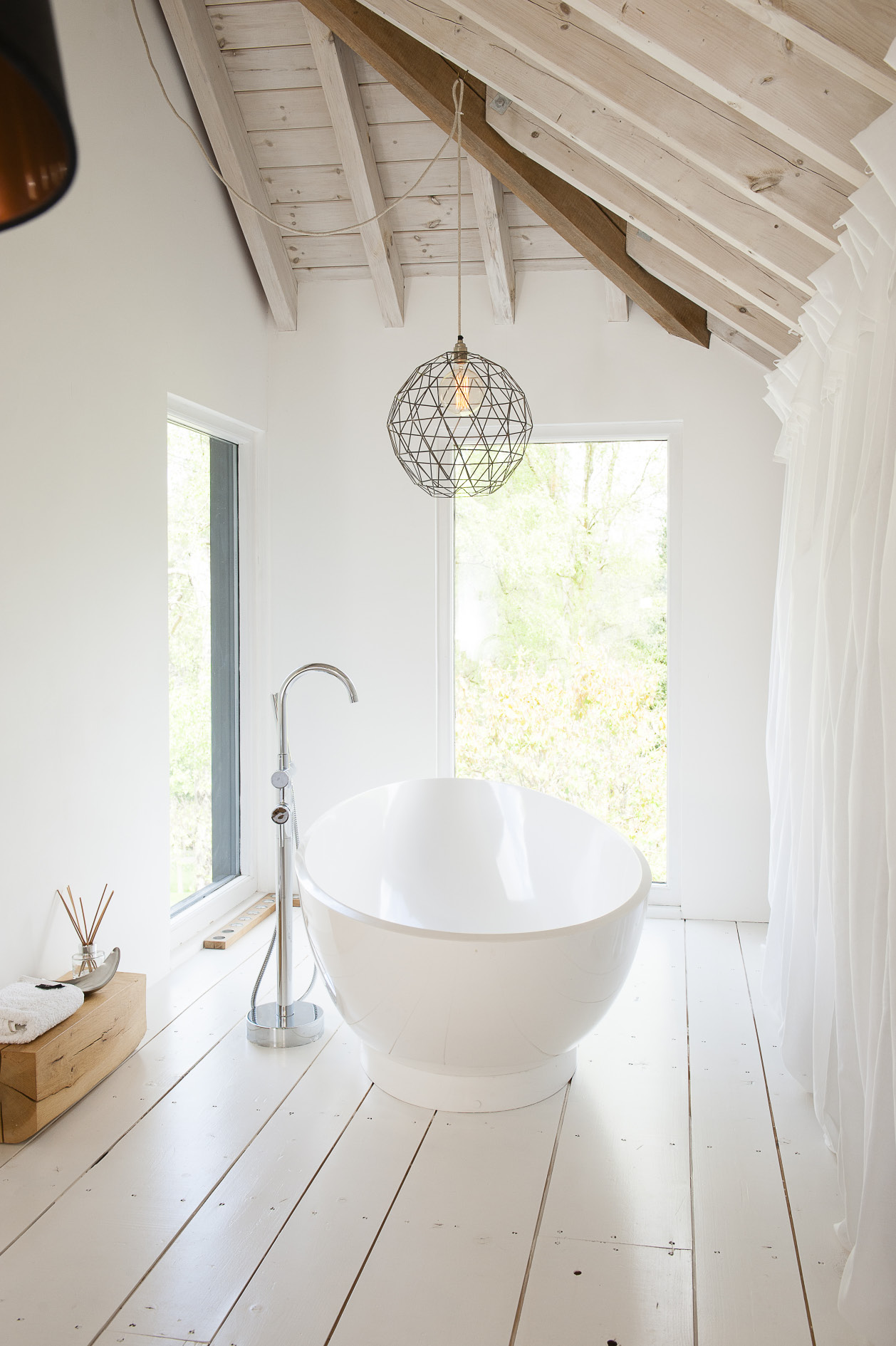 In one corner of the master bedroom a contemporary free-standing bath has been set in a double-aspect alcove overlooking the garden while at the other end is a spacious wet room