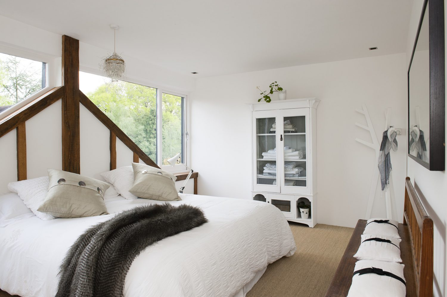 The large window overlooking the treetops is also the headboard for the double bed in one of the guest bedrooms. Sue has cleverly mirrored the view on the opposite wall so one can lie in bed still looking out over the surrounding greenery