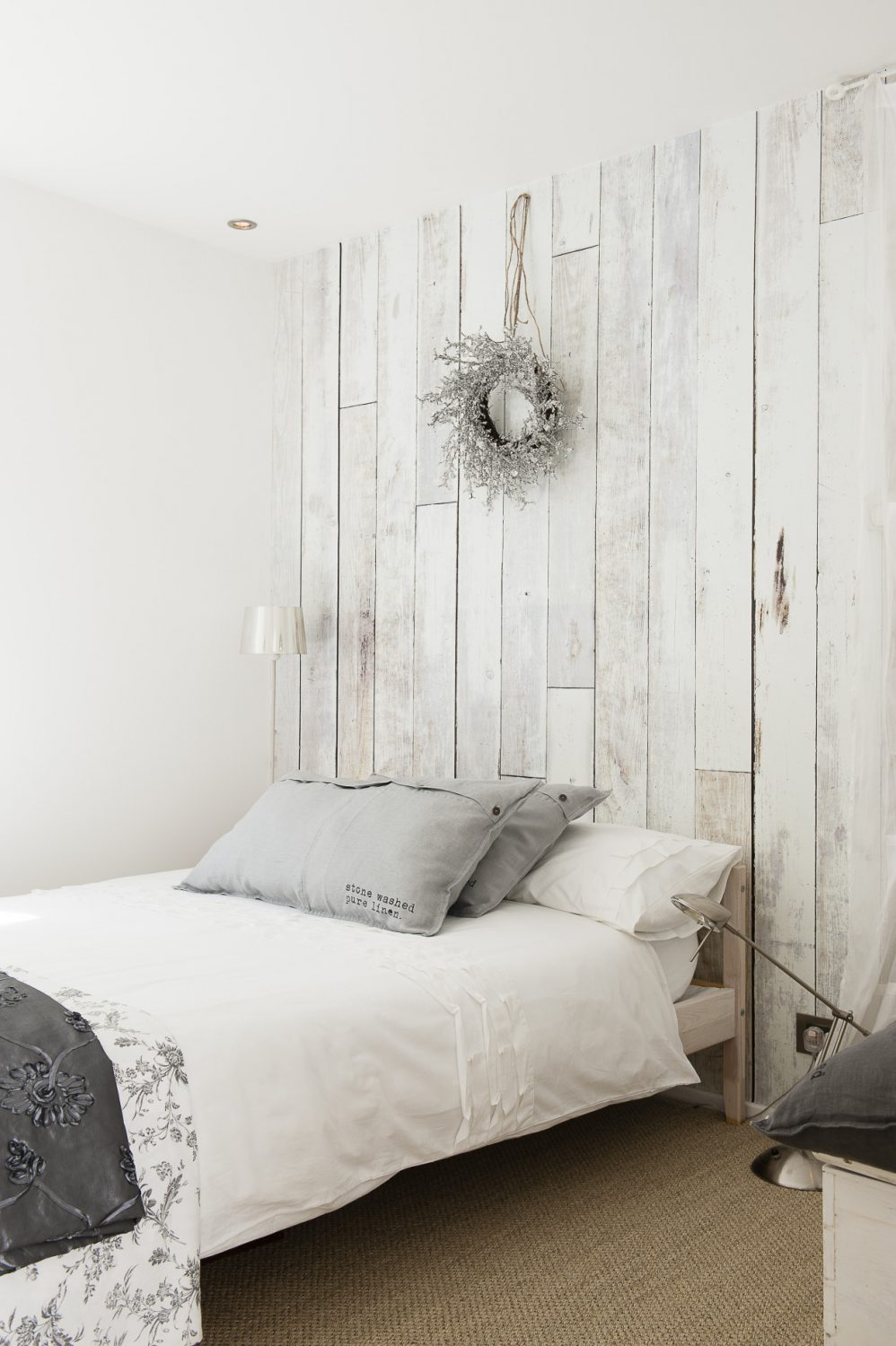 Wood panel effect wallpaper creates a trompe l'oeil on one wall of another guest room