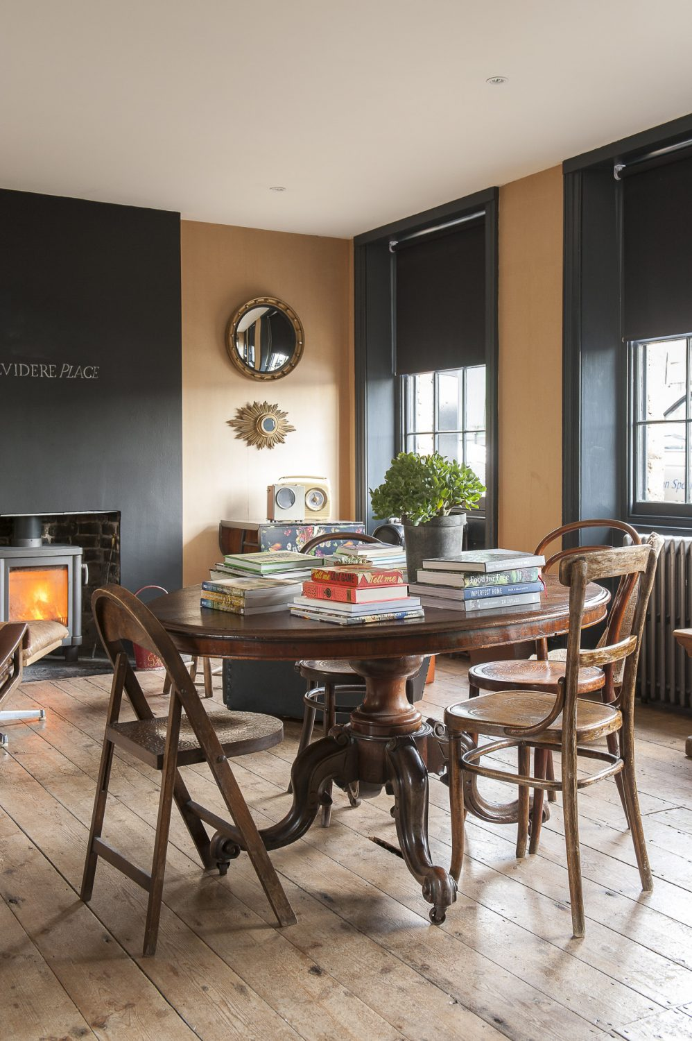 The living room has bare floorboards, blackboard paint on the chimney breast and, on closer inspection, brown wrapping paper on the walls – a surprisingly effective look
