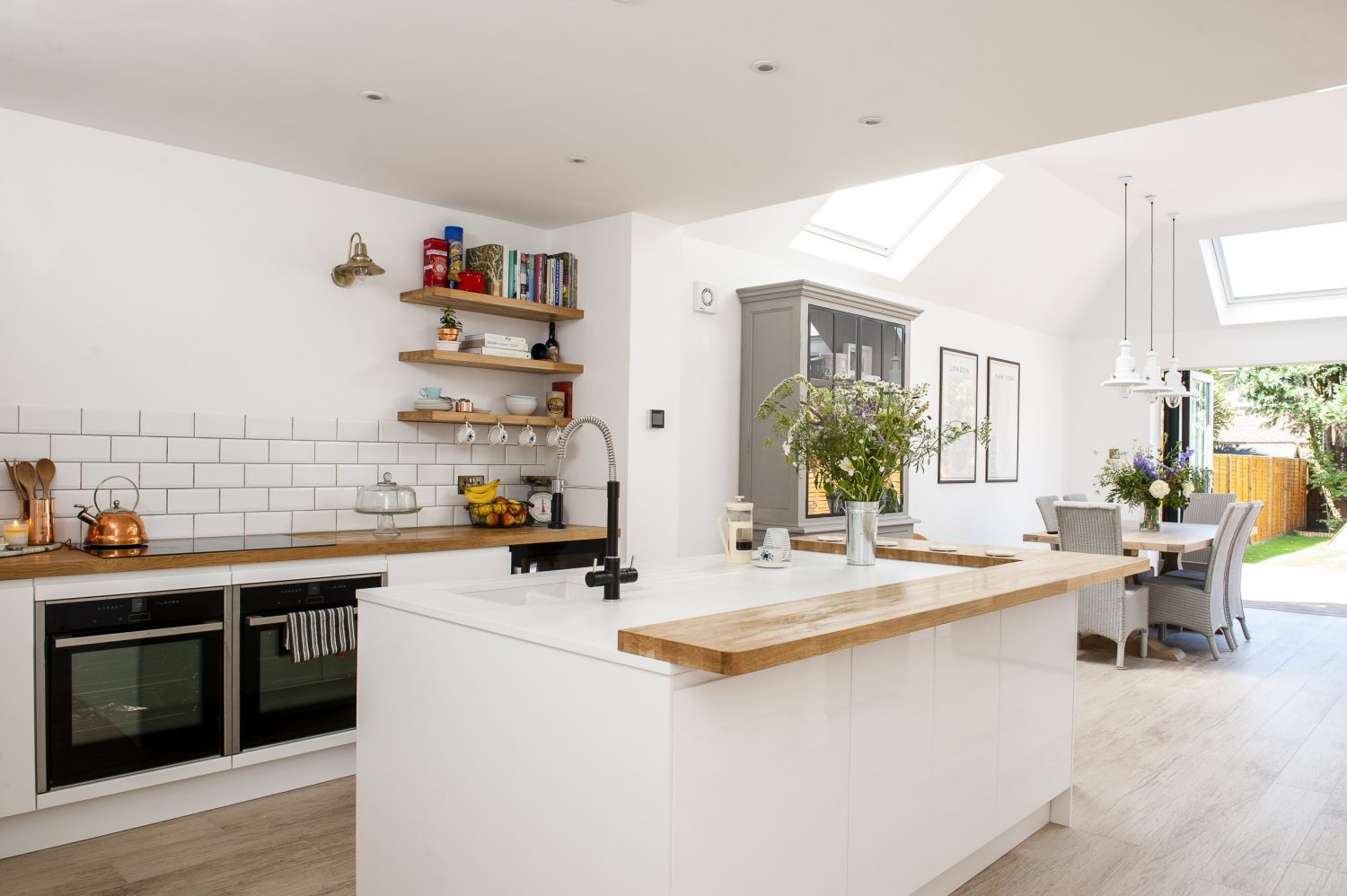 Wood is a recurring theme in the house, softening the all-white kitchen with the wide oak trim around the central island. The copper kettle is from John Lewis and the brass wall lights are from Cox & Cox. The oven is a Neff Slide & Hide, as made famous by Great British Bake Off
