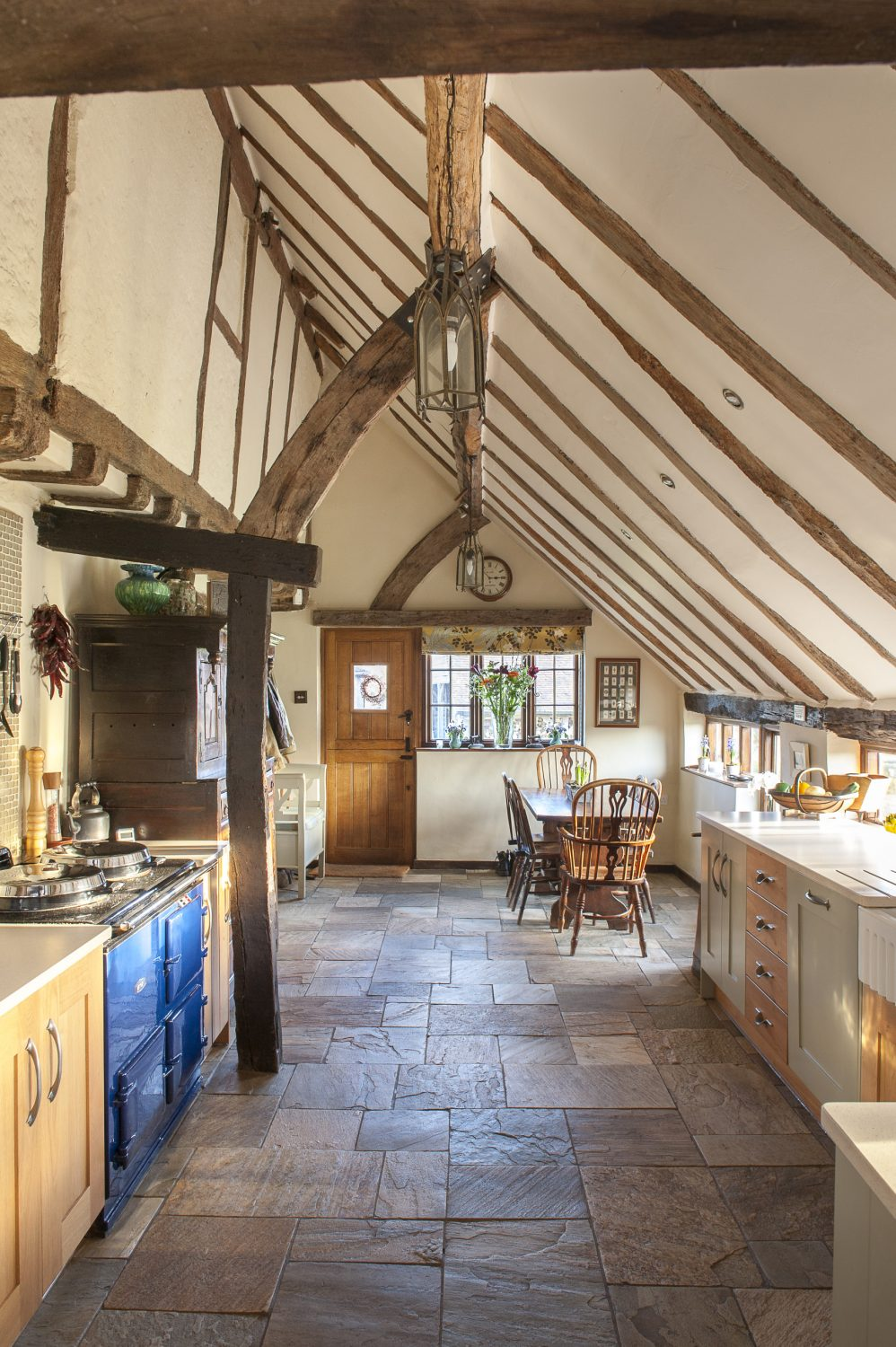 The first room you enter, from the box-edged gravel drive, is the kitchen. It is under a cat-slide roof at the back of the house, with the ceiling raised to the roof, revealing what was once the exterior rear wall and windows of the farmhouse
