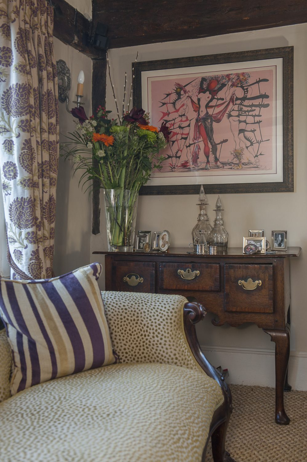 The couple bought this Salvador Dali lithograph, from the Femmes des Fleurs series and dated 1939, in Paris. It hangs above a chaise longue that Sarah had re-upholstered by Steve Burton in Appledore