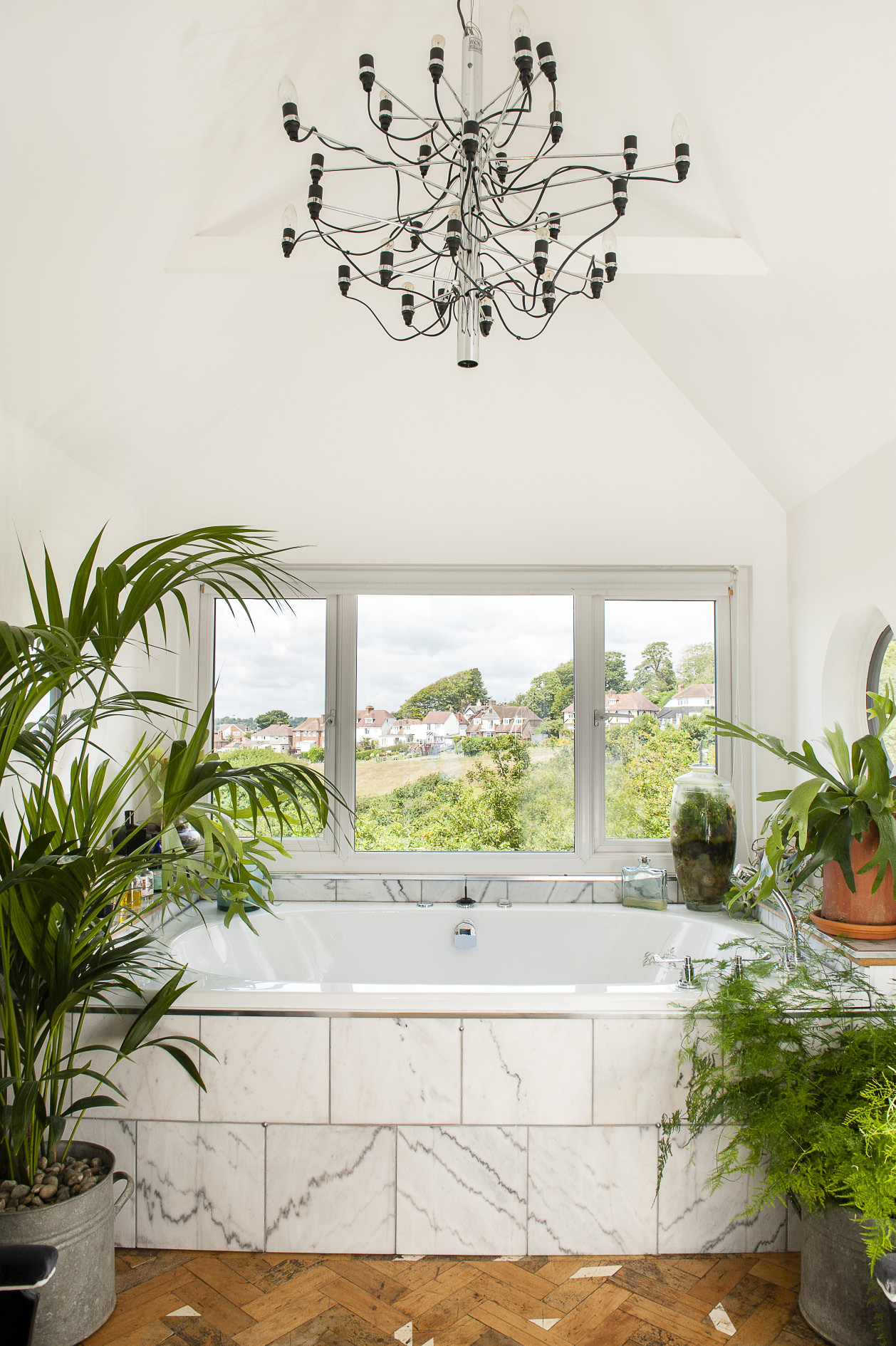 The plant-filled master bathroom has views over the Bourne valley. The chandelier is a 1958 design by Gino Sarfatti from Flos
