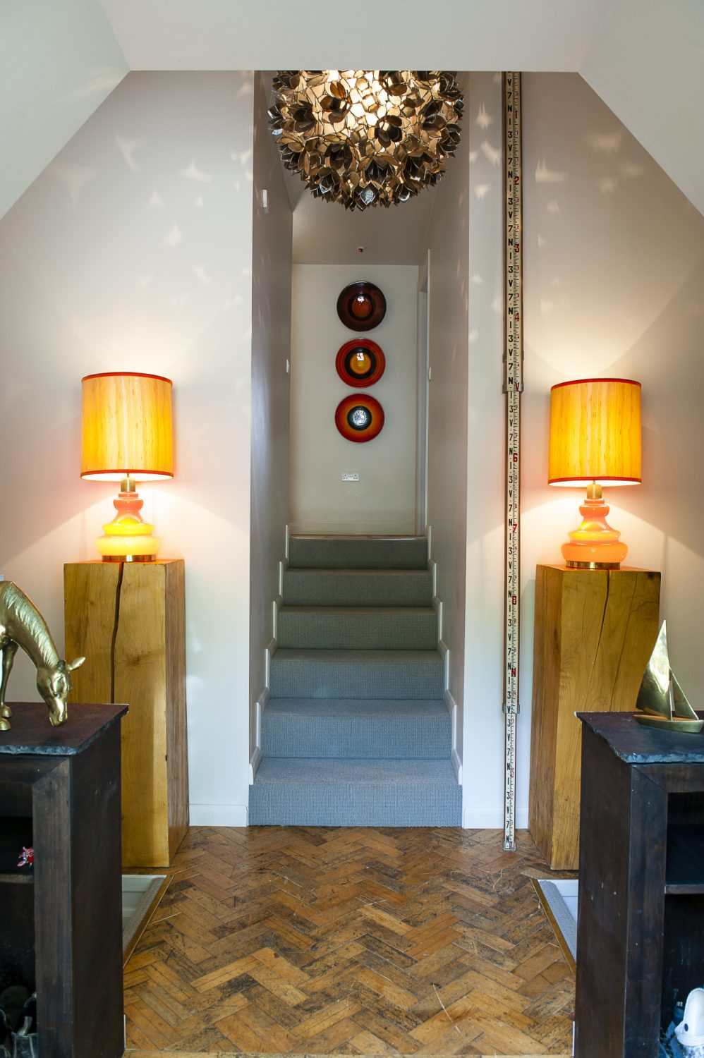 The hallway has two flights of steps down and one up. The three plates are part of a limited edition set of nine by Poole Pottery, commemorating the alignment of the planets in the year 2000