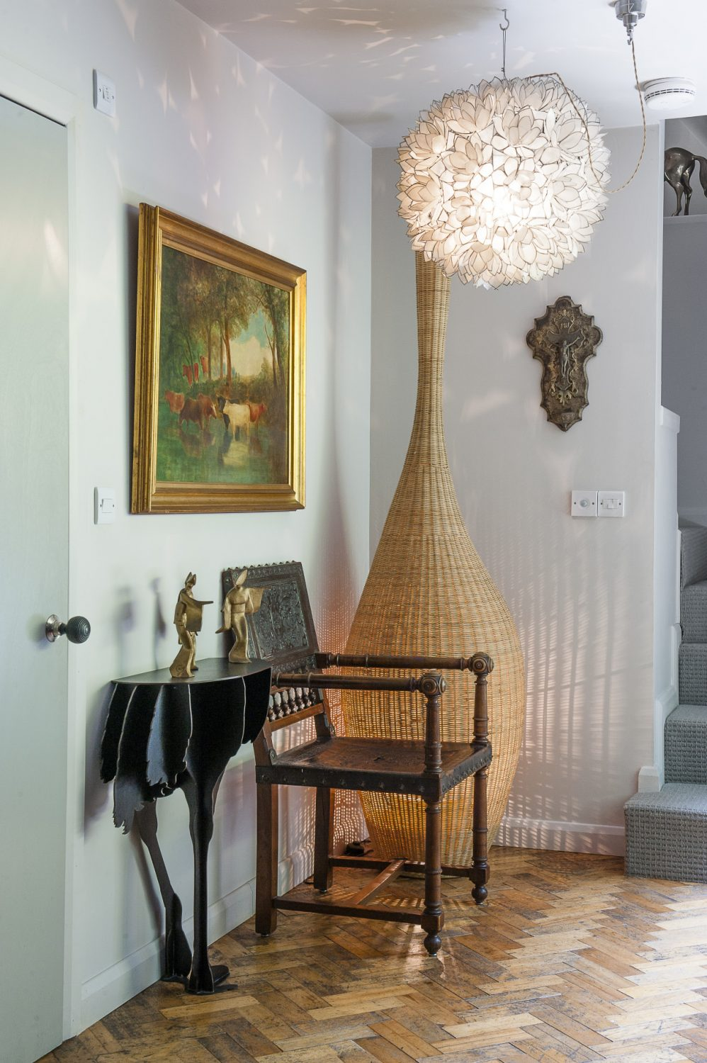 The wicker bowling pin lamp was from the Conran Shop and the Diva Ostrich table is by iBide from Abigail Ahern. The 18th century tooled leather French chair is a family heirloom, as is the oil painting above it. Sebastien laid the salvaged parquet himself