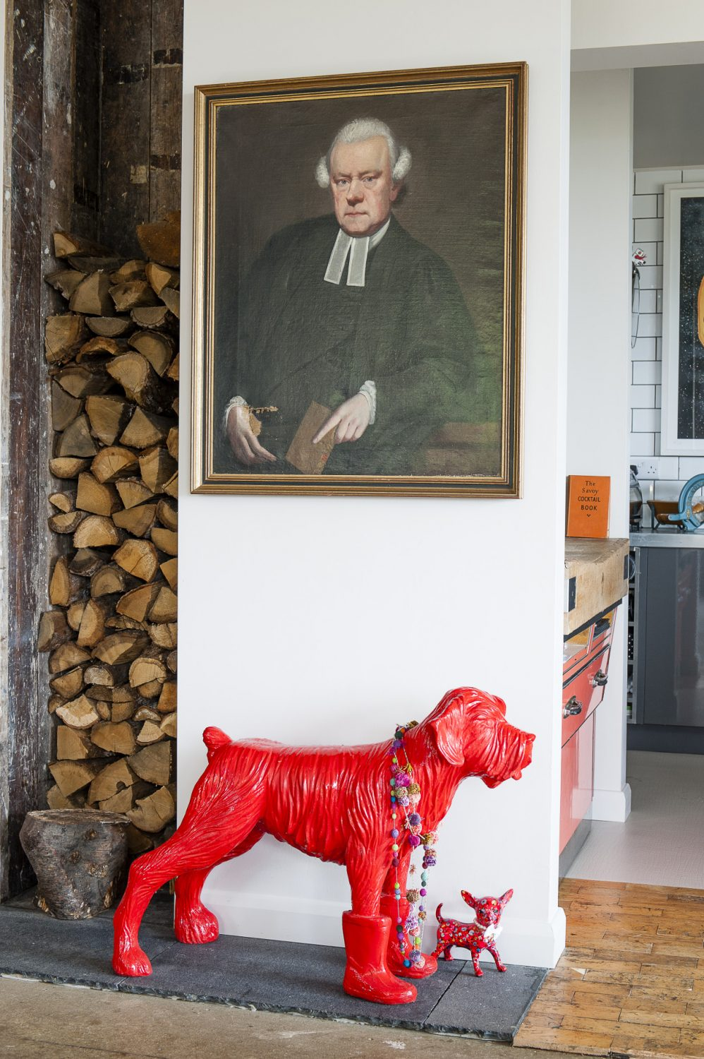 Above a life-sized red dog - in wellington boots - by Belgian sculptor William Sweetlove hangs an oil of a severe 18th century gentleman