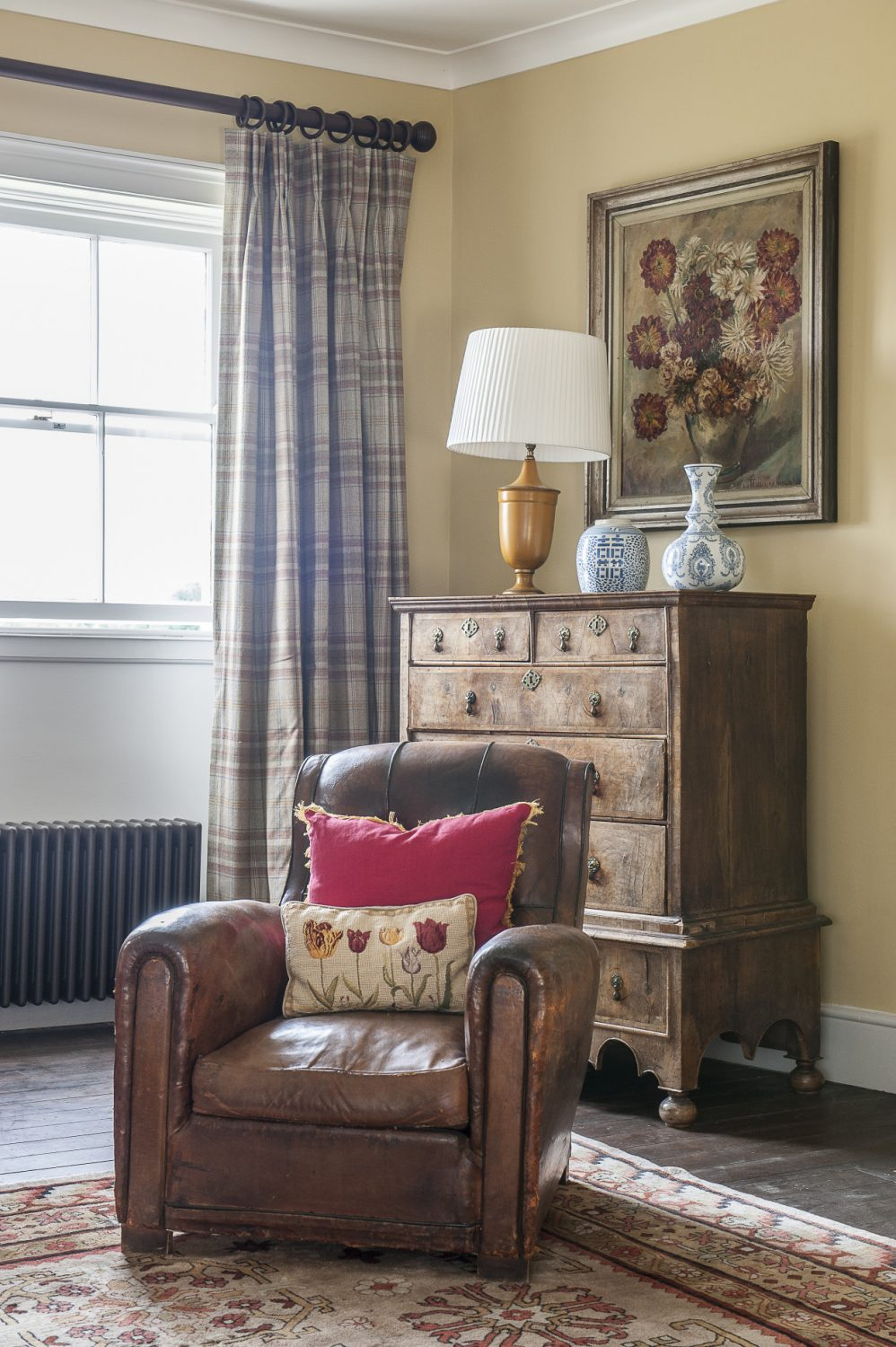 The leather club chair and the dahlia painting in Francis's bedroom were both found at Ardingly. The chest of drawers is a family piece. The plaid curtain fabric is by Colefax and Fowler