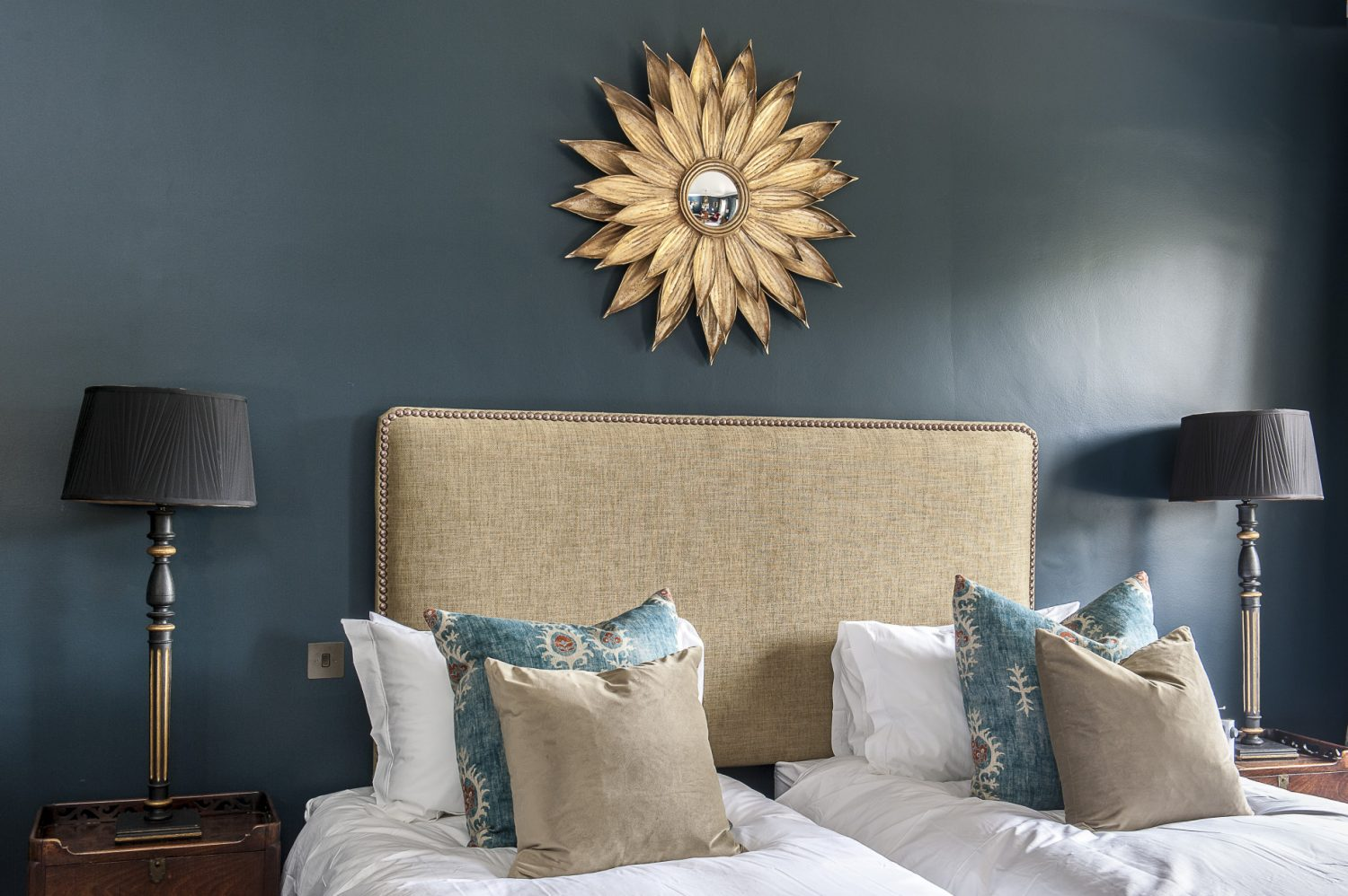 The walls of Henry's Room are painted in Hague Blue by Farrow & Ball. The sunburst mirror is from Barnstar, Rye