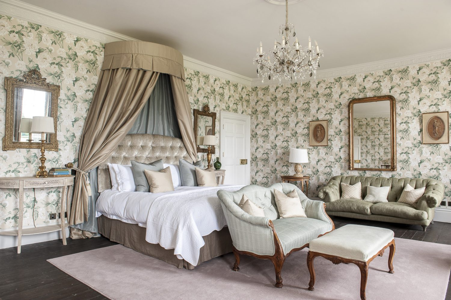 The largest of the twelve bedrooms, the FitzWalter Suite is decorated with Colefax and Fowler white rose paper. The built-in wardrobes are hidden behind wallpapered doors. Light pours in from three full-height windows with glorious views over the grounds. Francesca designed the corona over the bed in Colefax and Fowler silk