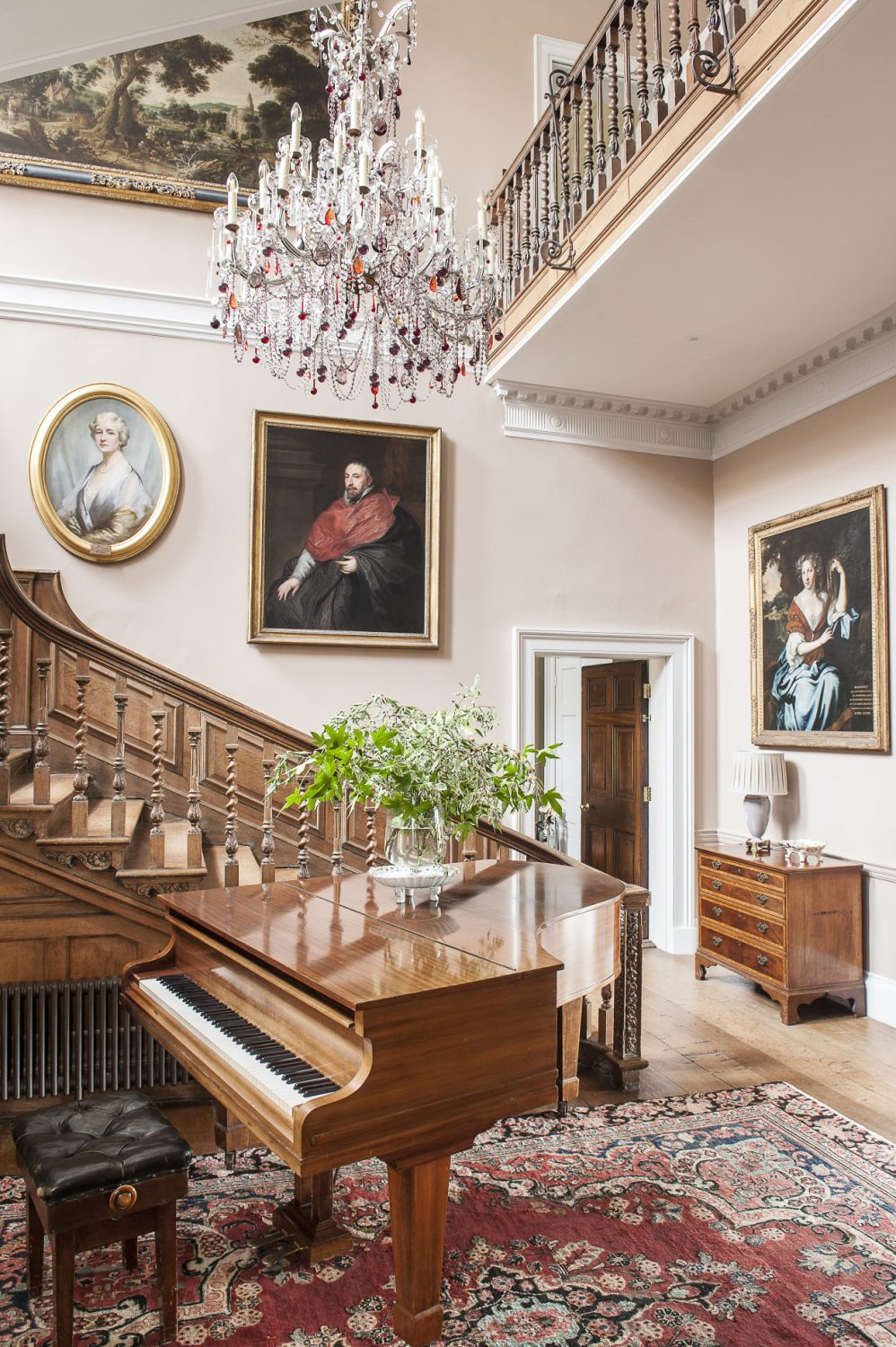 Julian's mother's piano sits at the bottom of the glorious main staircase, which is lined with ancestral portraits. Lord and Lady FitzWalter found the magnificent chandelier with multi-coloured drops in a 'shed' in Essex
