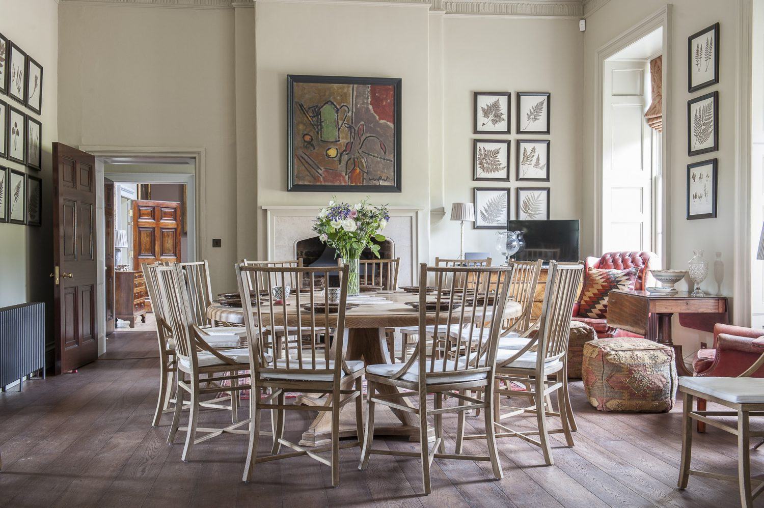 Light pours into the breakfast room through two floor-to-ceiling windows. The oval table was designed by Marcus and Francesca and made to order by the project's main contractors, BW May. The stone surround was custom made based on a fireplace in the cellar, with the FitzWalter coat of arms added.The painting over it is by Luke Hannam from McCully & Crane Art, Rye. Marcus found the wonderful collection of leaf pressings in the attic