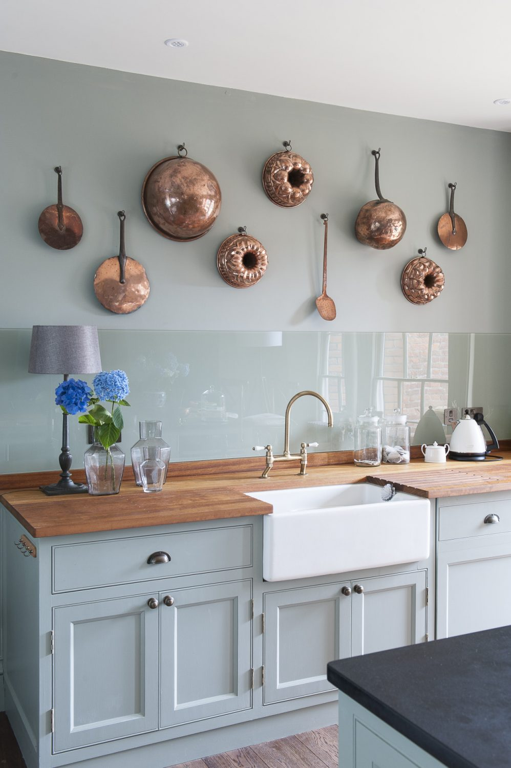 The shaker-style units and island in the kitchen were custom-built and painted in Pigeon by Farrow & Ball by the builders- BW May. The copper pans were from Ardingly