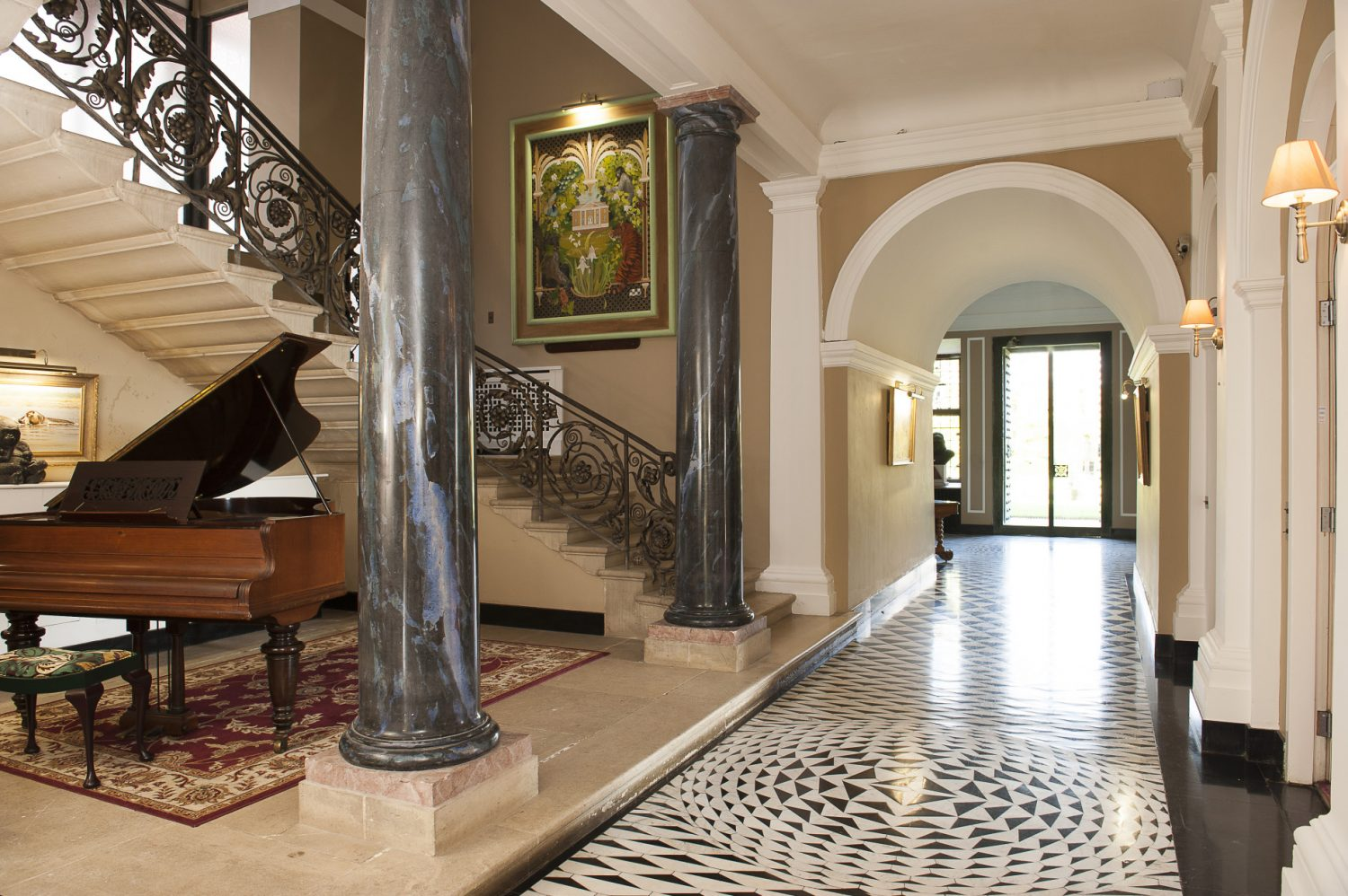 The dramatic tiled hall and passageway, which runs the length of the ground floor from east to west and is decorated with patterned black and white marble in varying concentric curves beneath a barrel-vaulted ceiling
