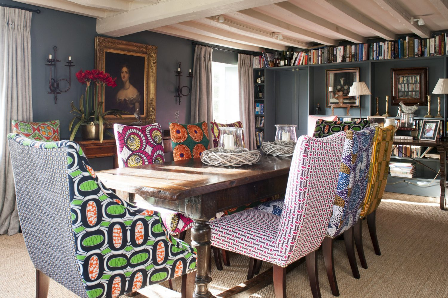 In the dining room the upholstered chairs which surround an antique refectory table are each covered in an entirely different African fabric