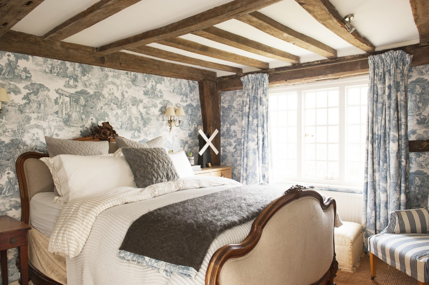 The first floor is home to a very pretty spare room featuring a French-style upholstered bed and blue Toile de Jouy wallpaper, curtains and trim