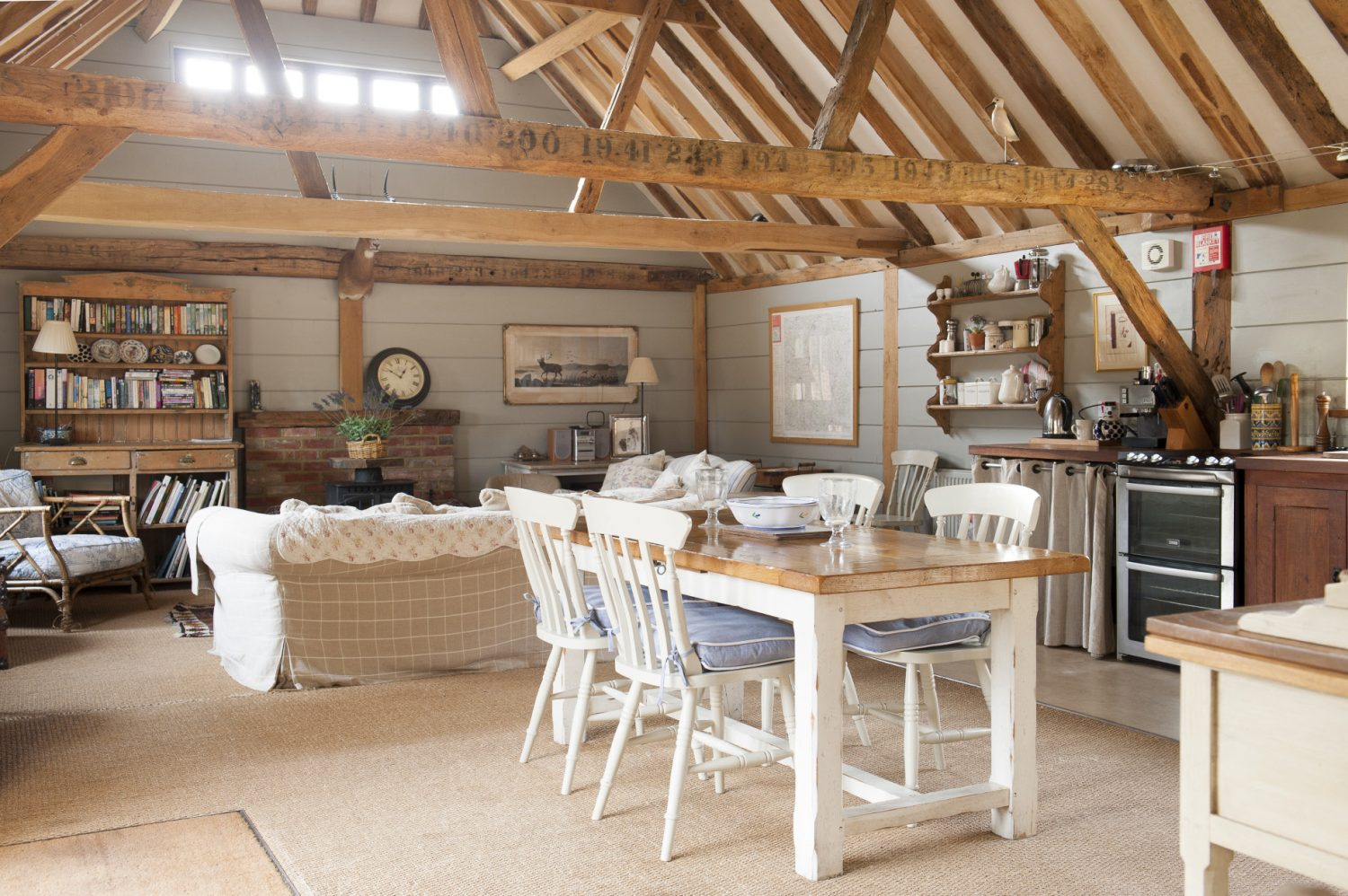 The Wylies' holiday let is reached by an outside staircase. Once inside the oast you're met with the most gorgeous open-plan kitchen and living room, lined with pale-blue painted boards and honey-coloured beams. Stencilled black numbers on the beams are a reminder of the oast's former purpose
