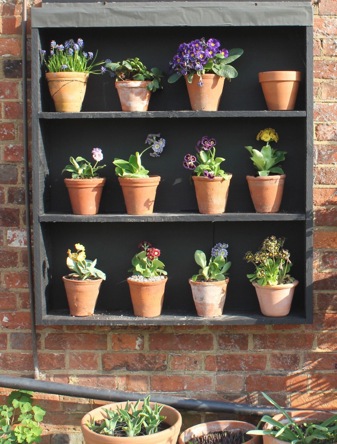 Terracotta pots look great against a black background. Here, shelves have been up-cycled to enhance a redbrick garden wall
