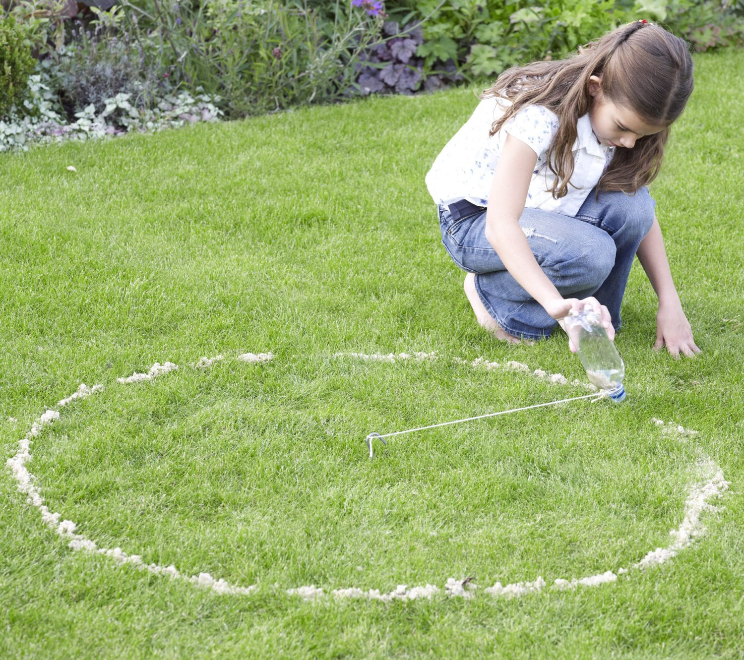 Ask a grown-up to use the bulb planter to make a hole along this circle every 4in (10cm) and leave the 'plug' of soil and grass by the side of the hole. The hole should only be about 2in (5cm) below the surface of the grass.