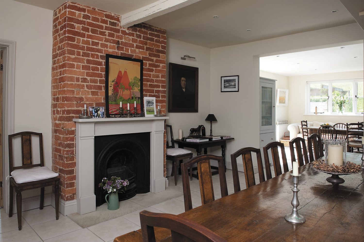 The spacious dining room leads off the kitchen. The poster of Kentish hop gardens above the fireplace is a former advertisement for British Rail; one of Mary's grandfather's thirteenth-century oak tables sits next to the fireplace