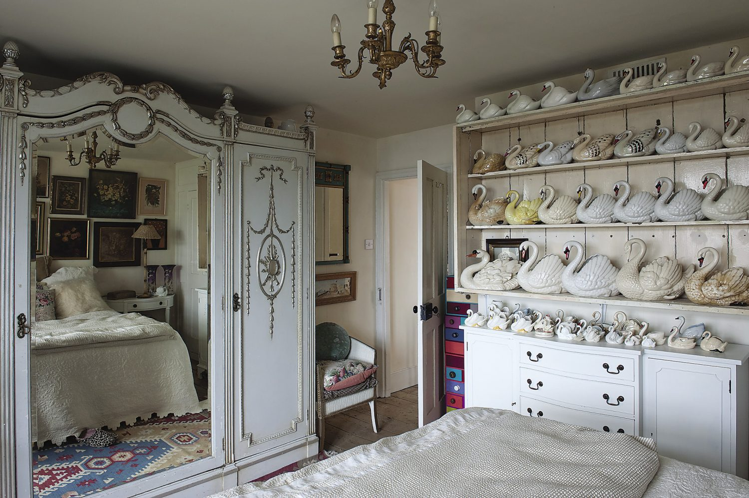 A huge mirror in the centre of the magnificent white and gold French wardrobe reflects light back into the room. Rows of vintage china swans are lined proudly on shelving: just a small proportion of Helen's huge collection
