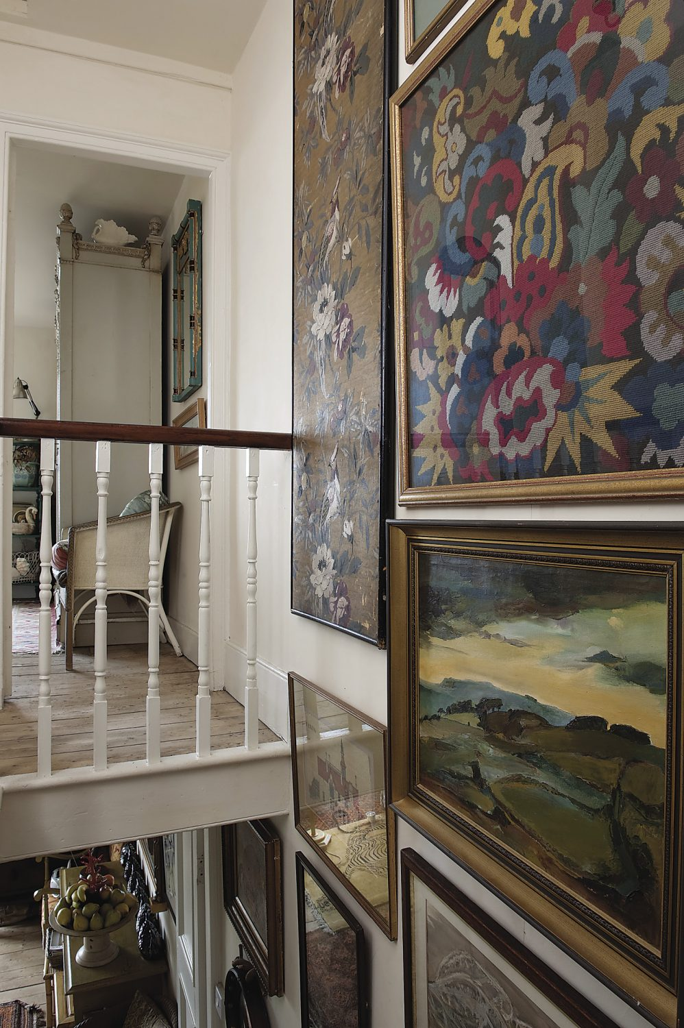 The walls by the staircase are covered in paintings, drawings and fabric panels