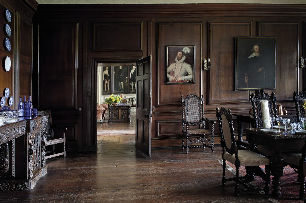 The walls of the State Dining Room are panelled in solid English oak that has darkened over the centuries and family portraits look down on the Jacobean-style dining tables and chairs